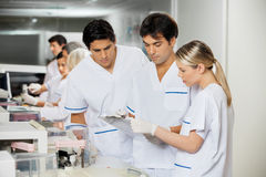 Technicians Discussing Over Clipboard. In laboratory Royalty Free Stock Photos