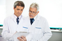 Technicians Discussing Over Clipboard. Male technicians discussing over clipboard in hospital Royalty Free Stock Photo