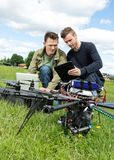 Technicians Discussing Over Digital Tablet By UAV. Young male technicians discussing over laptop and digital tablet by UAV helicopter in park royalty free stock image