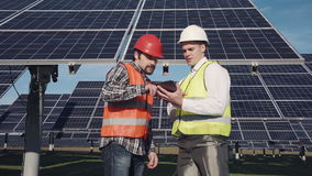 Technicians discussing solar panel array outside stock footage
