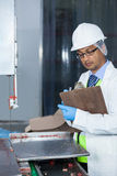 Technicians examining meat band saw. Technicians examining band saw machine at meat factory Stock Photo