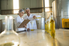 Technicians examining olive oil. In factory Stock Photos