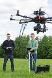 Technicians Flying UAV Helicopter in Park. Young technicians flying UAV helicopter with remote control in park Royalty Free Stock Image