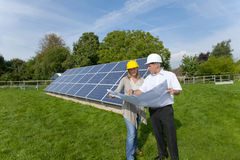 Technicians holding blueprints talking near large solar panels Stock Image