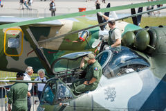 Technicians inspect attack helicopter with transport capabilities Mil Mi-24 Hind. Stock Photo