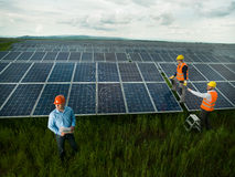 Technicians inspecting solar panel station. Top view of three men wearing protection equipment inspecting solar panel station, outdoors royalty free stock image