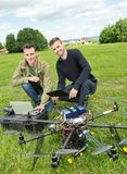 Technicians With Laptop And Digital Tablet By UAV. Portrait of technicians with laptop and digital tablet by UAV drone at park Royalty Free Stock Photography