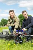 Technicians With Laptop And Digital Tablet By UAV. Portrait of male technicians with laptop and digital tablet by UAV at park Stock Image