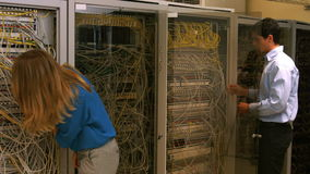 Technicians looking at open server locker. In high quality format stock video footage
