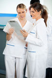 Technicians Reading Clipboard In Hospital Royalty Free Stock Images