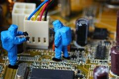 Technicians repair on computer mainboard. Miniature people Stock Photos