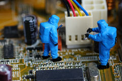 Technicians repair on computer mainboard. Miniature people Stock Images
