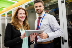 Technicians standing in server room with digital tablet Stock Photo