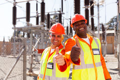 Technicians thumbs up. Two cheerful technicians giving thumbs up in substation Stock Photo