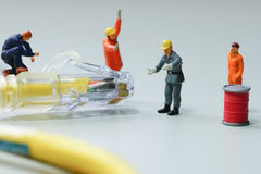 Technicians try to repair cable wire network. Miniature people Royalty Free Stock Photos