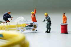 Technicians try to repair cable wire network. Miniature people Stock Image