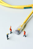 Technicians try to repair cable wire network. Miniature people Stock Images