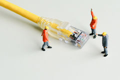 Technicians try to repair cable wire network. Miniature people Royalty Free Stock Image