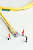 Technicians try to repair cable wire network. Miniature people Royalty Free Stock Photo