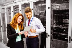 Technicians using digital tablet while analyzing server. In server room royalty free stock photos