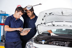 Technicians Using Digital Tablet By Damaged Car stock photo