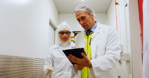 Technicians using digital tablet while walking in corridor. At meat factory stock video footage