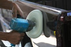 Automotive paint technician using grinder machine with wax on side of pickup , A part of the procedure to make a new color car. Technicians using equipment for stock photos