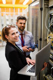 Technicians using laptop while analyzing server. Portrait of technicians using laptop while analyzing server in server room Stock Photo
