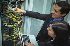 Technicians using laptop while analyzing server. In server room Royalty Free Stock Image