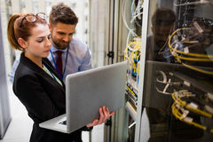 Technicians using laptop while analyzing server. In server room Stock Images
