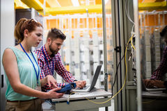 Technicians using laptop while analyzing server. In server room Royalty Free Stock Photo