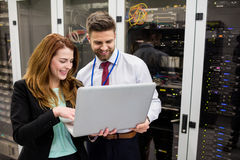 Technicians using laptop while analyzing server. In server room Stock Photo