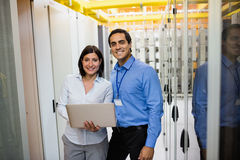 Technicians using laptop. Portrait of technicians using laptop in server room Stock Images