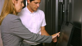 Technicians using laptop in server room stock video footage
