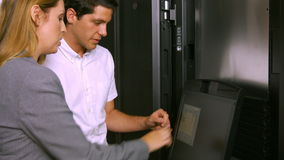 Technicians using laptop in server room. In high quality format stock video footage