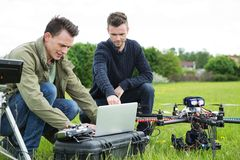 Technicians Using Laptop By UAV Drone. Young technicians using laptop by UAV drone in park Royalty Free Stock Images