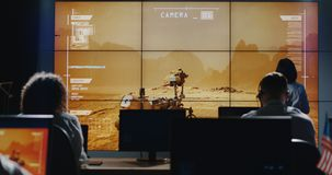 Technicians walking around in control room. Medium long shot of technicians walking around in control room while Mars Rover moving on digital screen stock photos