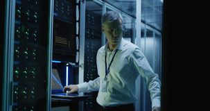 Technicians work on a laptop in a data center. Medium shot of technicians working on a laptop in a data center full of rack servers running diagnostics and royalty free stock image