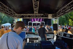 Technicians at work and People enjoying beautiful weather at festival and watching a band performing Royalty Free Stock Images