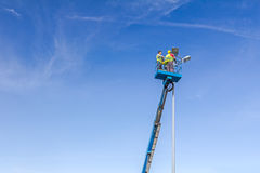 Technicians are working in a bucket high up on a spotlight tower Stock Images