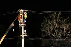 Technicians Working on Electrical Pole at Night. Technicians Installing High Voltage Equipment on Electrical Pole at Night Time Stock Image