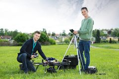 Technicians Working On UAV Helicopter. Portrait of happy technicians working on UAV helicopter in park stock photos