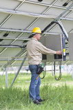 Technicians Working Under Solar Panels. Middle aged technician Working Under Solar Panels Stock Photos