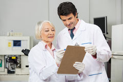 Technicians Writing On Clipboard In Laboratory. Male and female technicians writing on a clipboard in medical laboratory Royalty Free Stock Photography