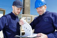 Technicians writing reading meter on clipboard outdoors. Technicians writing reading of meter on clipboard outdoors stock image