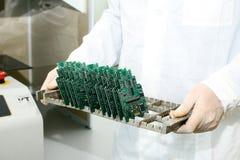 Technicien avec la carte d'ordinateur avec des puces Pièces de rechange et composants pour le matériel informatique Production de Photo stock