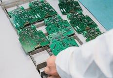Technicien avec la carte d'ordinateur avec des puces Pièces de rechange et composants pour le matériel informatique Production de Image libre de droits