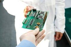 Technicien avec la carte d'ordinateur avec des puces Pièces de rechange et composants pour le matériel informatique Production de Photos libres de droits