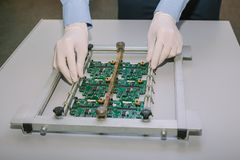 Technicien avec la carte d'ordinateur avec des puces Pièces de rechange et composants pour le matériel informatique Production de Images libres de droits