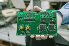 Technicien avec la carte d'ordinateur avec des puces Pièces de rechange et composants pour le matériel informatique Production de Images stock